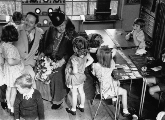 Maria Montessori with children in classroom (Black & White photograph)